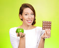 Apple over chocolate closeup portrait beautiful smiling young woman offering nutritious lime as an alternative to unhealthy square Stock Photo
