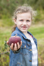 Apple picking a little girl holds a bright red while in focus shallow depth of field Stock Photo
