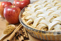 Apple pie homemade surrounded by red apples anise and cinnamon sticks Royalty Free Stock Photos