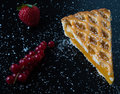 Apple pie slice on black table with currant and strawberry Royalty Free Stock Photo