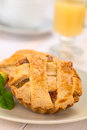 Apple pie small round with lattice crust with mint leaf on a plate hot punch in the back selective focus focus one third Stock Photography
