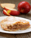 Apple pie on the white plate on wooden table Royalty Free Stock Photo