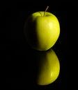 Apple on reflective ground green dark Stock Photos