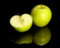 Apple on reflective ground green and halved dark Royalty Free Stock Photo