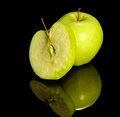 Apple on reflective ground green and slice dark Royalty Free Stock Images