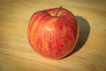Apple shadows stretching out onto a wooden cutting board. Nice and ripe and ready to be eaten. Royalty Free Stock Photo