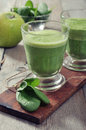 Apple and spinach smoothie in glass on a wooden background Stock Photography