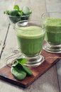 Apple and spinach smoothie in glass on a wooden background Royalty Free Stock Photos