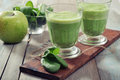 Apple and spinach smoothie in glass on a wooden background Stock Photo