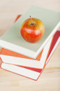 Apple on stacked books on table closeup of Stock Images