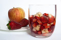 Apple and strawberry there is an in a glass with wine sugar there is in the background on a white Royalty Free Stock Photo