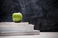 Apple on top of books with chalkboard. Royalty Free Stock Photo