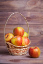 Apples in basket on wooden boards Stock Photo