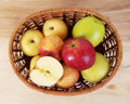 Apples in a basket on wooden table on top view full and half apple Stock Photos