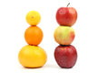 Apples and citrus stand vertically on each other on white backgr the background Royalty Free Stock Photos