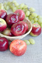 Apples and grapes harvest of in a basket on canvas Stock Image