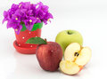 Apples, half of apple and bougainvillea flower in small pot Royalty Free Stock Photo