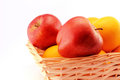 Apples and oranges in a basket with close up view with white background Royalty Free Stock Photo