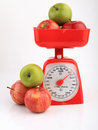 Apples on red weighing scale Royalty Free Stock Photo