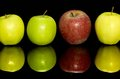 Apples in a row some green and red one on dark reflective ground Stock Photo