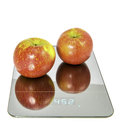 Apples on the scale symbolic photo for weight loss Stock Photos