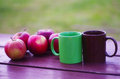 Apples and two tea cups on wooden table in the nature Stock Photos