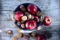 Apples and walnuts in shells filled in basket top shot autumn sunlight red shiny wooden scene on the wooden desk outdoors fall Royalty Free Stock Photo