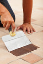 Applying the joint material on ceramic floor tiles closeup worker hand Stock Image