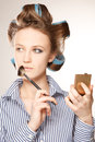 Applying make up young woman in curler in her hair and one eye with she is Royalty Free Stock Photos