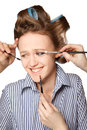 Applying make up young woman in curler in her hair and one eye with she is expressing her emotions with multiple hands Royalty Free Stock Image