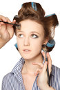 Applying make up young woman in curler in her hair and one eye with she is expressing her emotions with multiple hands Stock Photography