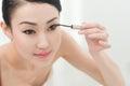 Applying mascara beautiful young woman on her eyelashes Royalty Free Stock Photo