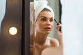 Applying a mascara young woman is after bath Stock Images