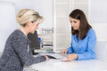Appointment at a specialist for finance female customer and adv adviser sitting desk talking about contract or business solutions Stock Image