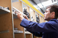 Apprentice checking stock levels in store room holding component Royalty Free Stock Image