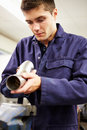 Apprentice engineer checking component on factory floor close up of Stock Image