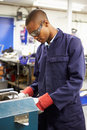 Apprentice engineer working on factory floor by himself Stock Photos