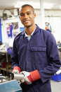 Apprentice engineer working on factory floor smiling to camera Stock Images