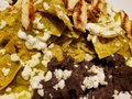 approach to plate of chilaquiles in green sauce with strips of roasted chicken and refried beans, traditional mexican food