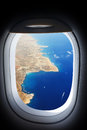 Approaching island holiday destination, jet plane window sea land view. Royalty Free Stock Photo