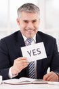 Approved cheerful grey hair man in formalwear holding a paper with yes sign on it while sitting at her working place Stock Photography