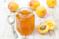 Apricot confiture in a glass jar and fresh apricots horizontal on the white wooden table Royalty Free Stock Image