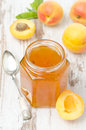 Apricot confiture in a glass jar and fresh apricots top view on the white wooden table Royalty Free Stock Photo