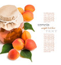 Apricot jam in a glass jar with ripe bright apricots on a white leaves background Stock Photos