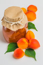 Apricot jam in a glass jar with ripe bright apricots on a white leaves background Stock Image
