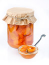 Apricot jam in a jar covered paper with a spoon Royalty Free Stock Photo