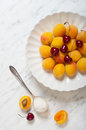 Apricots and cherries on a plate marble table Stock Photos