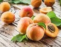 Apricots and its cross-section on the old wood Royalty Free Stock Photo