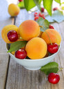 Apricots and sweet cherries in blue bowl on wooden table Royalty Free Stock Photo
