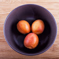 Apricots three inside a brown cup over wooden background Stock Image
